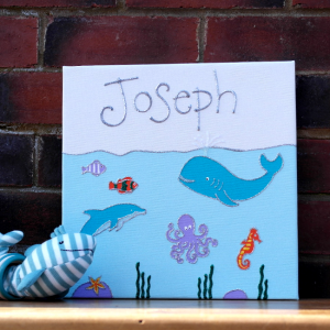 A personalised canvas picture set under the deep blue sea including huge blue whales and sweet dolphins, a long legged octopus, serene seahorse and jazzy fish. Seaweed growing at the bottom of the ocean.