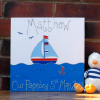 A personalised canvas picture of a small blue sail boat complete with blue flags sailing on the deep blue sea with two birds in the sky and a red anchor in the water. Finished with the child's name and date of birth in silver glitter.