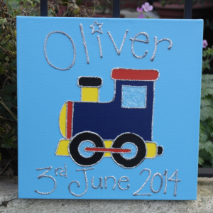 A personalised canvas picture of a dark blue, yellow and red train with big black wheels and blue windows on a blue background.