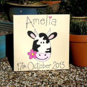 A personalised canvas picture of an adorable black and white cow holding a pink flower in its mouth.