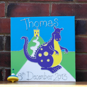 A personalised canvas picture complete with childs name and date of birth in silver glitter. The canvas picture shows a huge purple dragon with yellow spots and a yellow tummy standing in front of a castle on a hill.