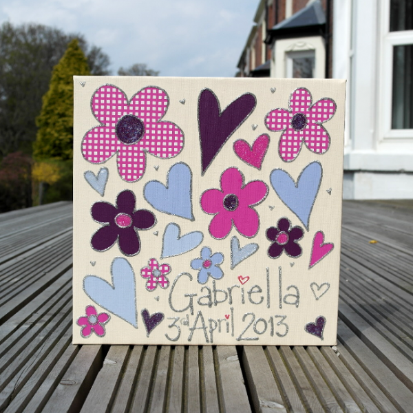 A personalised canvas picture including the childs name and date of birth. Gorgeous, vibrant purple and pink flowers and hearts on a cream background.