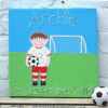A personalised canvas picture of a little footballer in a white and red strip holding a football on a field in front of a goal.