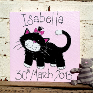A personalised canvas picture of a cute black kitten with white paws and a white tail tip, wearing a pink bow in its hair.