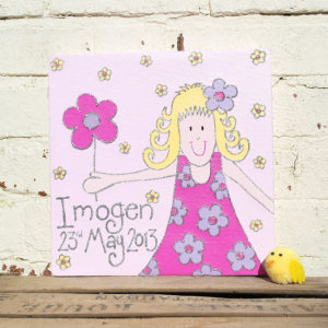 A personalised canvas picture of a little girl wearing and pink and purple flowery dress, with a purple flower in her hair and a pink flower in her hand.