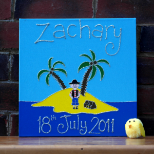 A personalised canvas picture of a pirate island complete with palm trees and yellow sand and a small pirate standing next to a treasure chest.