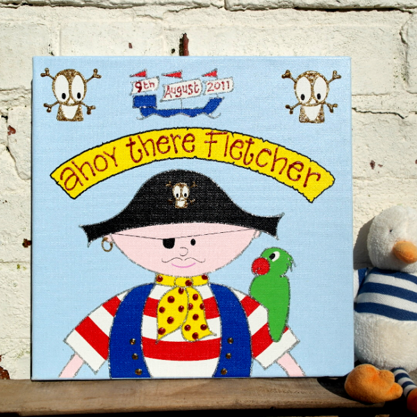 A personalised canvas print of a pirate wearing a red and white stripey shirt and blue waistcoat with an eyepatch and pirates hat. Above the pirate is a banner, skull and cross bones and pirate ship. The pirate has a parrot on its arm.