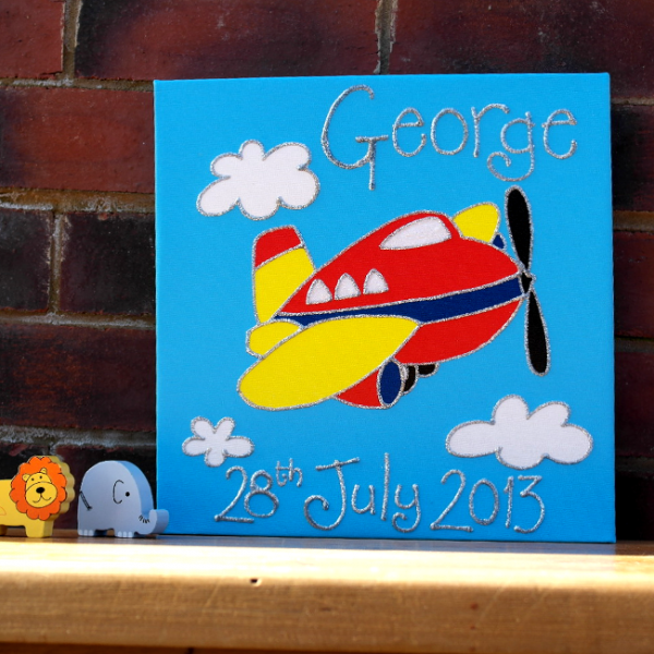 A personalised canvas picture of a red and yellow plane with white windows and a black propeller. White clouds and a blue sky background.