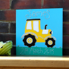 A bold yellow tractor personalised canvas picture with huge black wheels and silver trims. Riding along a deep green field with blue sky background and personalised with childs name and date of birth in glitter.