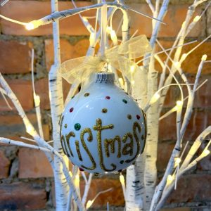 A white bauble with gold glitter hand written wording on it hanging on a white tree with lights.