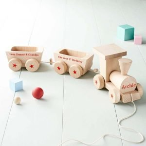 A gorgeous wooden train and carriage set crafted with sturdy light wood and decorated with a red non-toxic paint to add personalisation details.