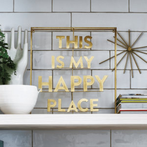 A lovely piece of wall art which says This is my Happy Place. Made from gold styled metal and attached to a metal frame.