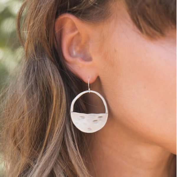 A circular pair of earrings where the bottom half is silver but the top section is open with a hook earring fastening.