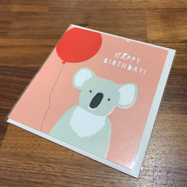 A card with a pink background and an image of a Koala bear holding a red balloon. The words Happy Birthday are embossed and printed in white.