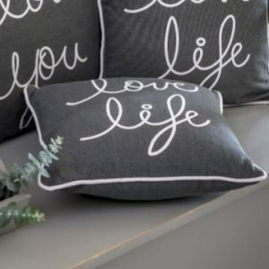 A grey cushion with the wording Love Life printed in white and piped with a white cord.