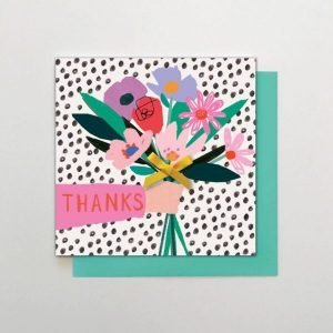 A square thank you card with an illustration of an arm holding out a bunch of bright flowers on a black and white spotty background. Hand finished with a yellow bow on the bunch of flowers. Blank in side and Thanks a bunch on the outside