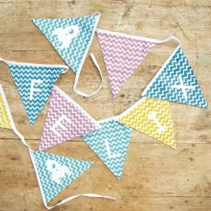 cotton bunting in blue turquoise pink and yellow chevron patterned flags. Personalised with a name in white letters