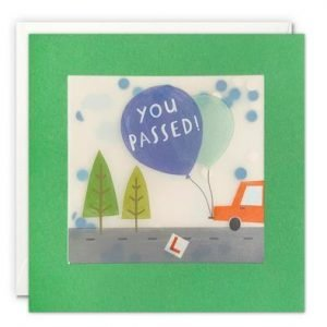 A square card with a green border around it. The image behind the border is of a car with a balloon and the words You Passed on the balloon. The image is covered by a translucent packet which has colourful confetti inside of it. When you shake the card the confetti moves around inside of it.