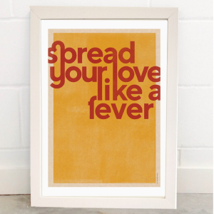 A print with a mustard coloured background with a white border and the words spread you love like a fever printed in burnt orange colour in an unusual type font which has a retro feel.