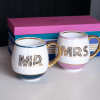 A pair of mugs which are printed for a happy couple. The mugs are striped around the bottom of them and have the words Mr on one and Mrs on the other. The pair og mugs come in a colourful striped box.