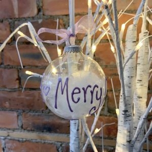 A clear glass bauble filled with white feathers personalised with hand written wording around the bauble.