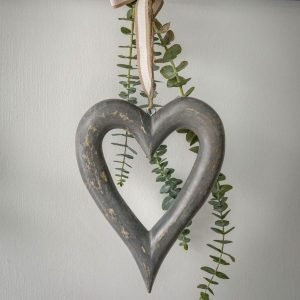hand carved chubby grey wooden heart hanging on a natural twine.