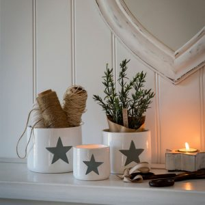 A set of three white pots with grey stars hand painted on the front of them