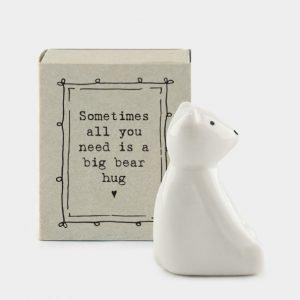 A sweet little porcelain bear keepsake kept in a little cardboard matchbox with the wording 'SOmetimes all you needs is a big bear hug' printed on it.