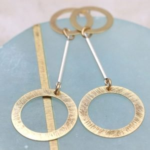 A pair of scratched golden double hoop earrings from jewellery design com[any POM