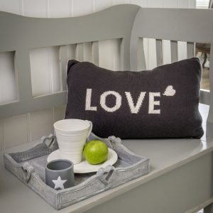 A double sided cushion with the word Love on it. Knitted in grey with cream wording on one side and cream with grey wording on the other.