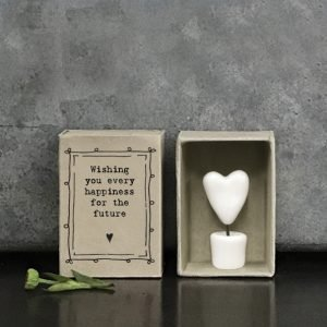 A little ceramic keepsake of a heart on a stick in a pot, with a cardboard matchbox with the wording 'Wishing you every happiness for the future.'