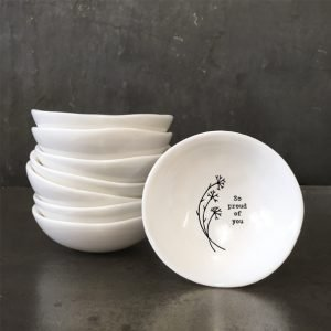 A mini white ceramic trinket dish with a flower design and the words 'So Proud of You' imprinted on it.