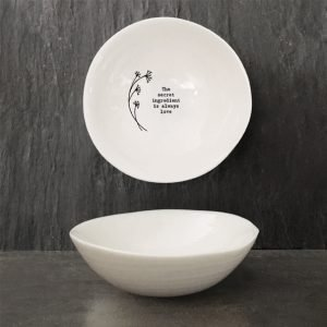 A sweet white ceramic dish from British design company East of India, with a flower design and the wording 'The Secret Ingredient is Always Love' imprinted on it.
