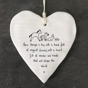 A white ceramic wobbly heart from British design company East of India. The words Here sleeps a boy with a head full magical dreams, a heart full of wonder and hands that will shape the world' imprinted on it.