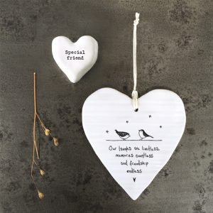 A white ceramic wobbly hanging heart from British design company East of India, with the words ' Our Laughs are Limitless, memories are countless and friendship endless.' imprinted on it.