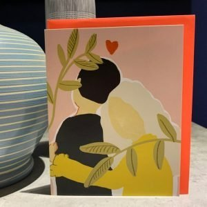 A colourful card with a lovely affectionate couple on it with a love heart printed above them