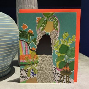 A stunning colourful card with a woman with long black hair looking after her house plants.