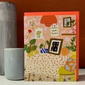 A colourful blank greetings card that could be used as a New Home card or could be sent for any other reason. The image is of a table in a room that has alot of plants and patterns with a print on the wall saying Home Sweet Home.