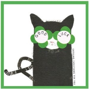 A good luck card with a fun illustration of a black cat in four leaf clover glasses and good luck written on the glasses
