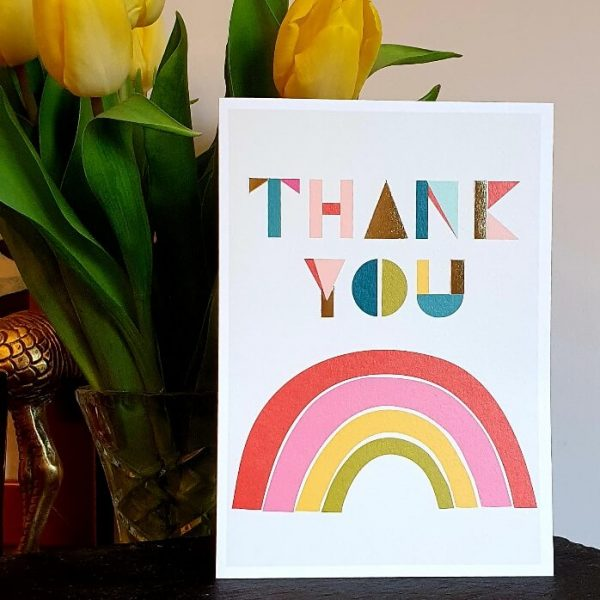 A thank you card with a brightly coloured rainbow and a colourful thank you