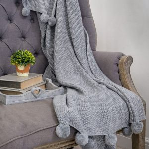 A delicate moss stitch knitted throw in grey with 10 fluffy pom poms at each end. 100% acrylic 170cm by 130cm