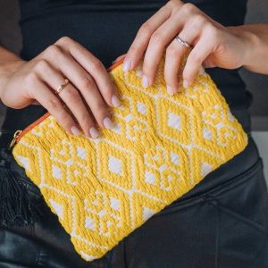 A handmade yellow and white woven fabric cosmetic pouch with zip fastening.
