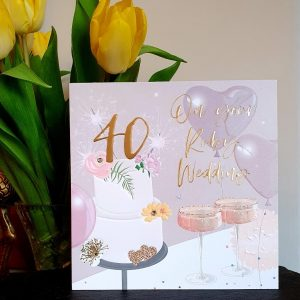 A large luxury 40th ruby wedding anniversary card with a cake and champagne glasses, embellished with clear crystal gem stones and gold foiled lettering with a large 40 on top of the cake and the words On Your Ruby Wedding