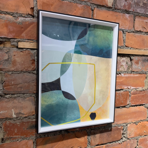 A contemporary abstract print in blues and greens in a black frame.