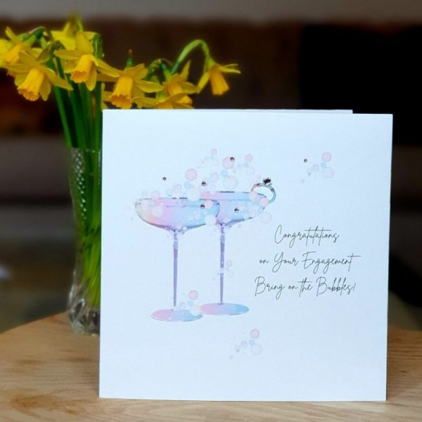 A shimmering white card with a beautiful rainbow illustration of a pair of cocktail glasses. Hand finished with genuine crystals. Congratulations on your engagement, bring on the bubbles.
