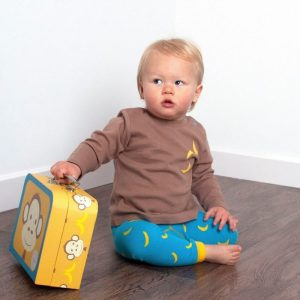 A child holding the suitcase from the Marley Monkey gift set and wearing the cute monkey leggings and long sleeved t shirt top