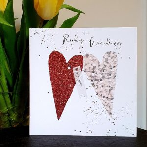 A large ruby wedding anniversary card with 2 large hearts, one is ruby colours the other neutral, a tag reads 40 years. Hand finished with crystals