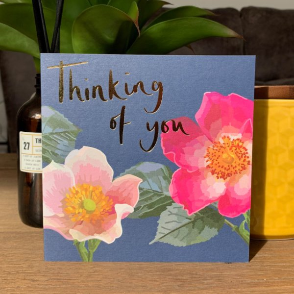 A gorgeous card from Sarah Kelleher with painted open flowers and the words Thinking of You printed and finished in foil effect.
