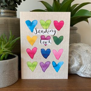 A gorgeous colourful card with hearts all over it and the words Sending Love printed in the middle of it.