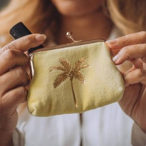 A yellow velvet coin purse with a gold clip top fastening and a gold foil palm tree decoration on the front.